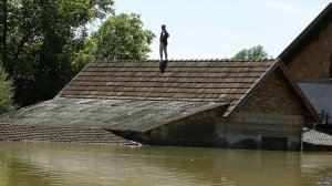 A Serbian man stands atop his home.