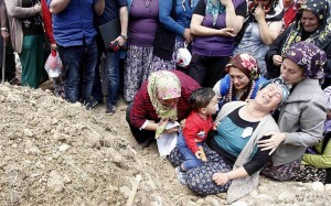 Women mourn at the graves of the miners.
